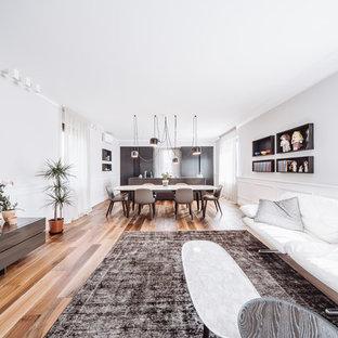 Esempio di un soggiorno design aperto con pareti bianche, pavimento in legno massello medio, nessun camino, TV a parete e pavimento marrone