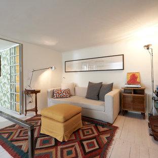 Foto de sala de estar tipo loft, mediterránea, pequeña, sin chimenea, con paredes blancas, suelo de madera pintada, televisor colgado en la pared y suelo blanco