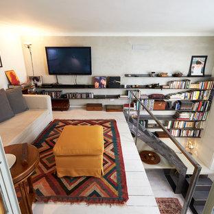 ミラノの小さい地中海スタイルのおしゃれなファミリールーム (ライブラリー、グレーの壁、塗装フローリング、壁掛け型テレビ、白い床) の写真