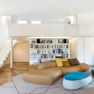 Immagine di un ampio soggiorno contemporaneo aperto con libreria, pareti bianche e parquet chiaro