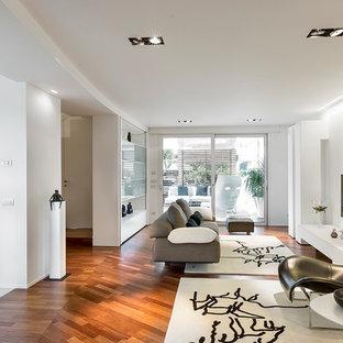 Foto di un grande soggiorno design aperto con pareti bianche, pavimento in legno massello medio e TV a parete