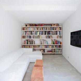 Inspiration för ett funkis allrum, med ett bibliotek, vita väggar, betonggolv och en väggmonterad TV