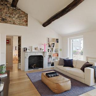 Immagine di un grande soggiorno minimal con pareti bianche, parquet chiaro, camino classico e cornice del camino in pietra