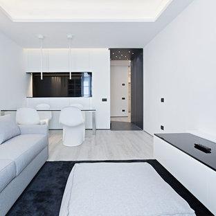 Foto de salón abierto, moderno, con paredes blancas, suelo de madera clara y televisor colgado en la pared
