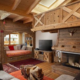 Ispirazione per un soggiorno rustico aperto con cornice del camino in legno, TV autoportante, pareti bianche, pavimento in legno massello medio, camino classico e pavimento marrone