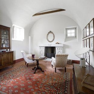 Foto de sala de estar cerrada, de estilo de casa de campo, de tamaño medio, con paredes blancas, suelo de ladrillo, chimenea tradicional y marco de chimenea de piedra