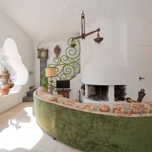 Idee per un ampio soggiorno mediterraneo con pareti bianche, soffitto a volta, camino classico, cornice del camino in intonaco e TV autoportante