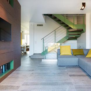 Foto di un soggiorno minimal di medie dimensioni e aperto con pareti bianche, pavimento in gres porcellanato e TV a parete