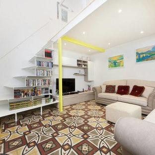 Esempio di un piccolo soggiorno contemporaneo aperto con libreria, pareti bianche, pavimento in cemento, nessun camino, parete attrezzata e pavimento multicolore