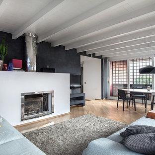 Foto di un grande soggiorno design aperto con pareti nere, parquet chiaro, camino lineare Ribbon, TV a parete e cornice del camino in metallo