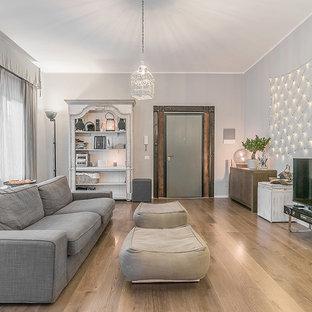 Ejemplo de sala de estar nórdica con paredes grises, suelo de madera clara y televisor independiente