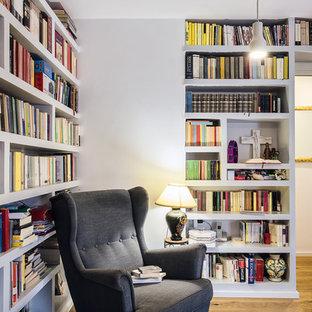 Idee per un soggiorno scandinavo con libreria, pareti grigie, pavimento in legno massello medio e pavimento marrone