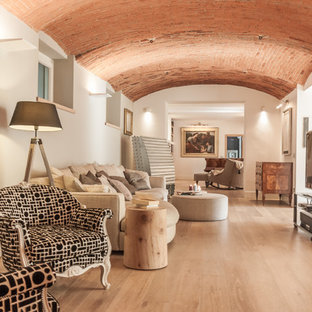 Immagine di un grande soggiorno mediterraneo aperto con pareti bianche, parquet chiaro, TV autoportante e pavimento beige