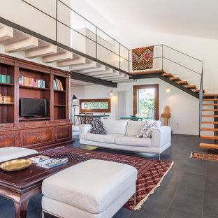 Ispirazione per un soggiorno contemporaneo aperto con pavimento grigio, sala formale, pareti bianche, camino classico e TV autoportante