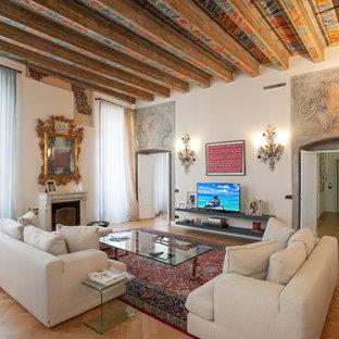 Esempio di un ampio soggiorno mediterraneo chiuso con pareti bianche, pavimento in legno massello medio, pavimento marrone, camino classico, cornice del camino in pietra e parete attrezzata