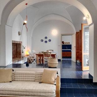 Idee per un soggiorno costiero di medie dimensioni e aperto con pareti bianche, pavimento con piastrelle in ceramica, camino classico, cornice del camino in mattoni, nessuna TV e pavimento blu