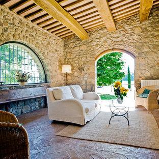 Idee per un grande soggiorno country aperto con pareti beige, camino classico, cornice del camino in mattoni e pavimento in terracotta