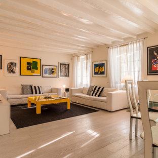 Esempio di un soggiorno design aperto con parquet chiaro, TV a parete, pareti bianche, nessun camino e pavimento beige