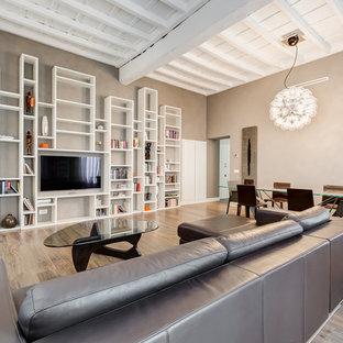 Esempio di un grande soggiorno minimal aperto con pareti beige, parquet chiaro, TV a parete, libreria, nessun camino e pavimento marrone