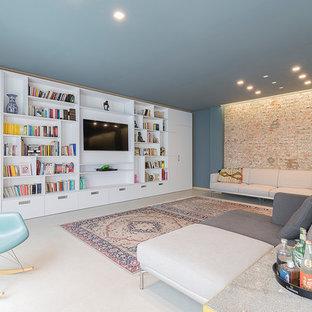 Immagine di un grande soggiorno contemporaneo con pavimento in cemento, pavimento grigio, libreria, pareti blu, nessun camino e parete attrezzata