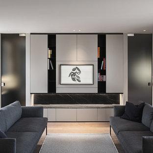 Foto di un piccolo soggiorno design aperto con libreria, pareti grigie, TV a parete, pavimento grigio e soffitto ribassato