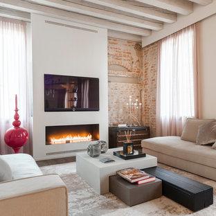 Esempio di un soggiorno contemporaneo aperto con pareti beige, camino classico, TV a parete e cornice del camino in intonaco