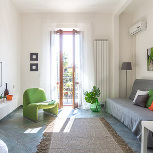 Foto di un soggiorno tropicale con libreria, pareti bianche, nessun camino e pavimento grigio