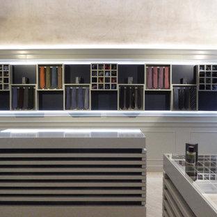 Imagen de biblioteca en casa abierta y boiserie, clásica, pequeña, con paredes beige, suelo de mármol, televisor retractable, suelo beige y boiserie