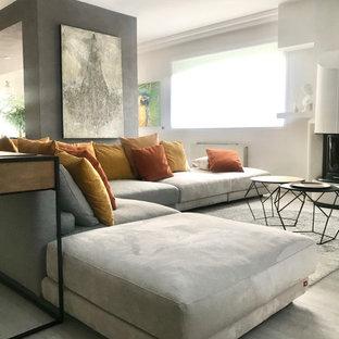 Esempio di un grande soggiorno minimalista aperto con pavimento in laminato, camino classico, pareti bianche, cornice del camino in intonaco, TV a parete e pavimento grigio