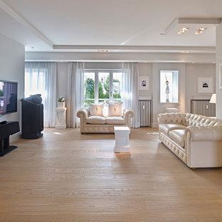 Idee per un ampio soggiorno classico aperto con parquet chiaro e TV a parete