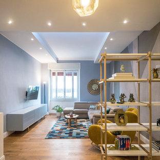Esempio di un soggiorno minimal con pareti blu, pavimento in legno massello medio, TV a parete e pavimento marrone