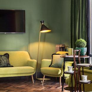 Idee per un soggiorno bohémian con pareti verdi, parquet scuro e TV a parete