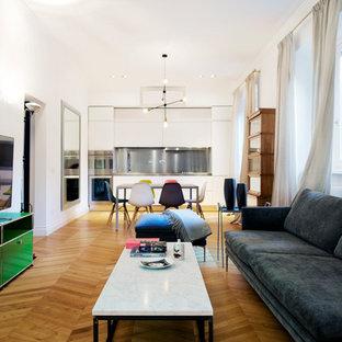 Esempio di un grande soggiorno minimalista aperto con pareti bianche, pavimento in legno massello medio e TV autoportante