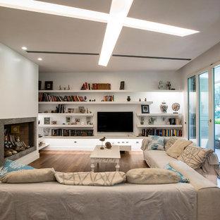 Esempio di un grande soggiorno minimal aperto con libreria, pareti bianche, pavimento in legno massello medio, camino classico, cornice del camino in pietra, TV a parete e pavimento marrone