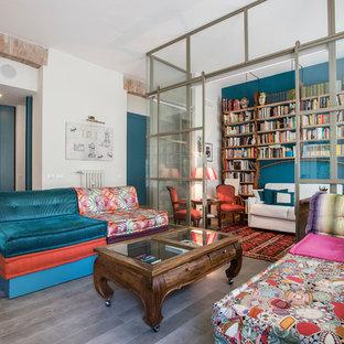Immagine di un soggiorno etnico con libreria, pareti blu e pavimento grigio