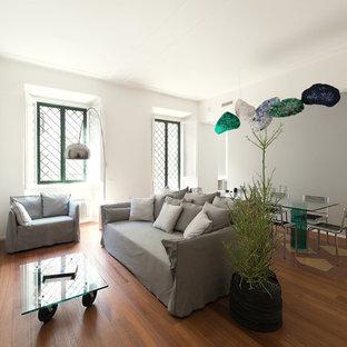 Immagine di un soggiorno contemporaneo di medie dimensioni e aperto con libreria, pareti grigie, pavimento in legno massello medio, camino ad angolo, cornice del camino in intonaco e pavimento marrone
