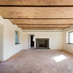 Idee per un piccolo soggiorno country chiuso con pareti bianche, pavimento in mattoni, camino classico, cornice del camino in pietra, pavimento rosa, soffitto a volta e pannellatura