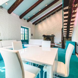 Modelo de salón para visitas abierto, minimalista, de tamaño medio, con paredes blancas, moqueta, chimenea tradicional, marco de chimenea de ladrillo, televisor retractable y suelo turquesa