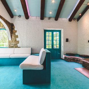 Foto de salón para visitas abierto, moderno, de tamaño medio, con paredes blancas, moqueta, chimenea tradicional, marco de chimenea de ladrillo, televisor retractable y suelo turquesa