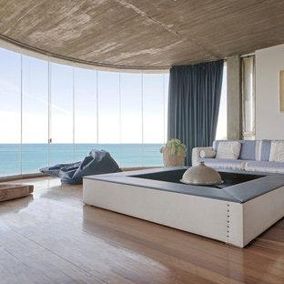 Idee per un soggiorno minimal aperto con pareti bianche, pavimento in legno massello medio e pavimento marrone