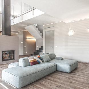 Idee per un soggiorno design aperto con sala formale, pareti grigie, parquet chiaro, camino bifacciale e cornice del camino in intonaco