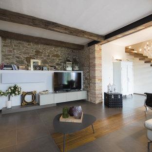 Esempio di un soggiorno eclettico di medie dimensioni e aperto con pareti bianche, TV autoportante, pavimento grigio e pareti in mattoni