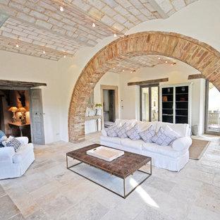他の地域の巨大なラスティックスタイルのおしゃれなLDK (白い壁、ライムストーンの床、標準型暖炉、石材の暖炉まわり、ベージュの床) の写真