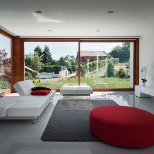 Idee per un soggiorno moderno aperto con pareti bianche, nessun camino, TV a parete e pavimento grigio