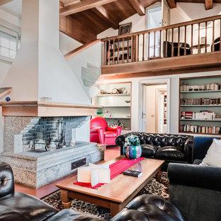 Esempio di un grande soggiorno country aperto con libreria, pareti verdi, pavimento in terracotta, camino classico, cornice del camino in pietra e pavimento arancione