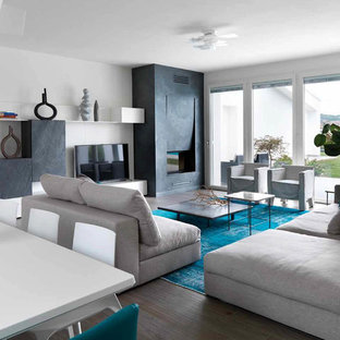 Immagine di un grande soggiorno contemporaneo aperto con pareti bianche, parquet scuro, cornice del camino in intonaco e TV autoportante