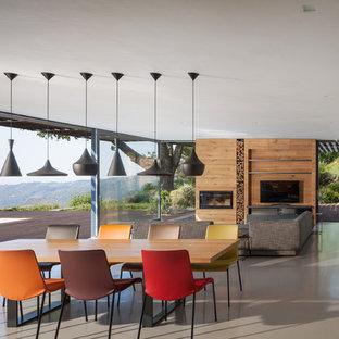 Imagen de sala de estar actual con paredes grises, suelo de cemento, estufa de leña, marco de chimenea de madera y televisor independiente