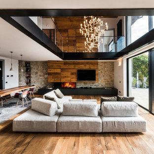 Idee per un ampio soggiorno design stile loft con pareti bianche, pavimento in legno massello medio, camino ad angolo, cornice del camino in legno, parete attrezzata e sala formale