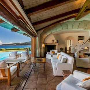 Ispirazione per un ampio soggiorno stile marino aperto con pareti bianche, pavimento in pietra calcarea, camino classico e cornice del camino in pietra