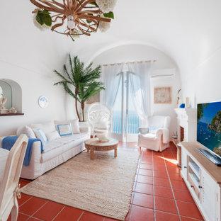 Idee per un grande soggiorno mediterraneo aperto con sala formale, pareti bianche, camino classico, cornice del camino in intonaco, parete attrezzata, pavimento marrone e soffitto a volta